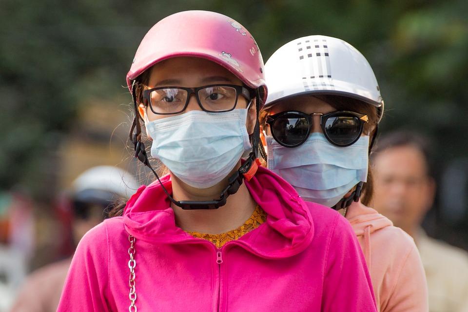 Due ragazze indossano la mascherina in mezzo al traffico