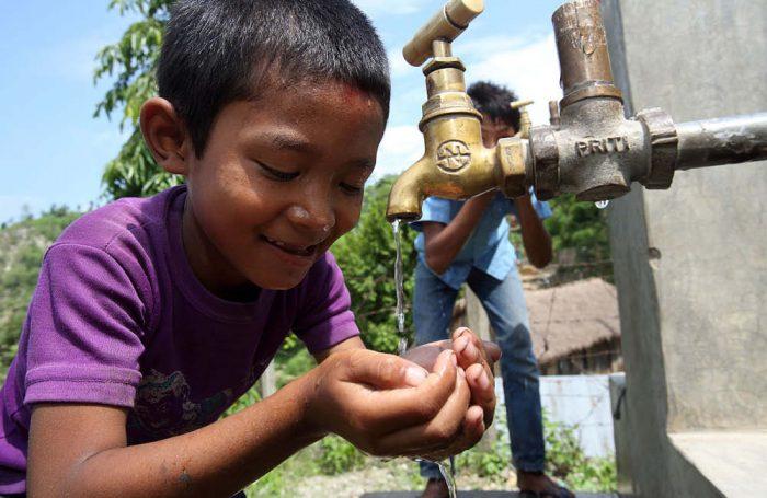 Un bambino beve dell'acqua da un rubinetto in Nepal