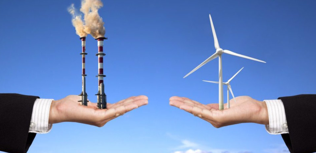 Una mano che sostiene delle turbine eoliche si oppone a un'altra mano che sostiene delle ciminiere