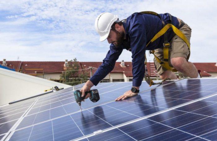 Un tecnico installa dei pannelli solari sul tetto di un edificio